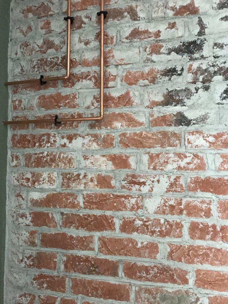 twee koperen leidingen over de muur geven het een extra stoere uitstraling