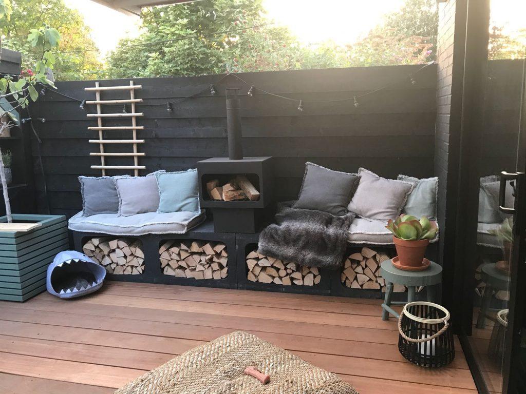 stoere tuin inrichten met zwarte schutting en buitenhaard